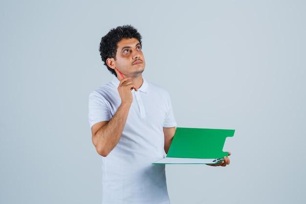 Jonge man die pen in eureka-gebaar opheft en notitieboekje in wit t-shirt en spijkerbroek vasthoudt en peinzend kijkt. vooraanzicht.