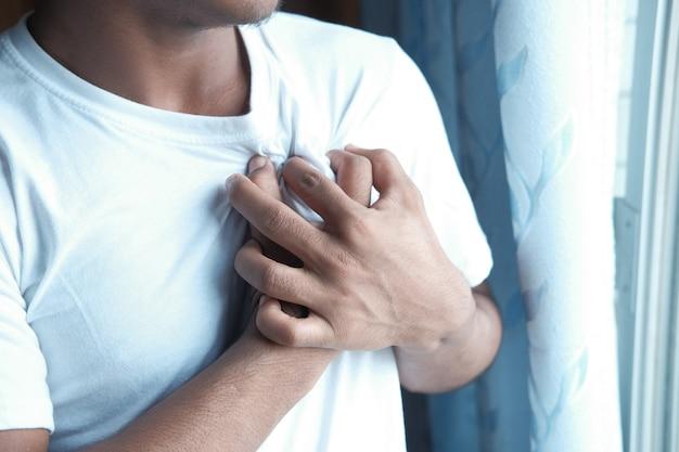 Jonge man die pijn in het hart lijdt en borst met hand vasthoudt