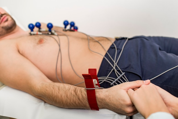 Jonge man die preventief electrocardiogram in het ziekenhuis doet