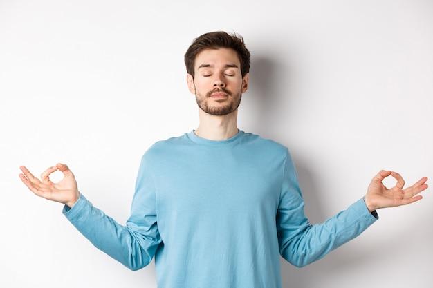 Jonge man die probeert te ontspannen in meditatie, kalm staat met uitgestrekte handen in zen mudra-gebaar, yoga beoefent op witte achtergrond