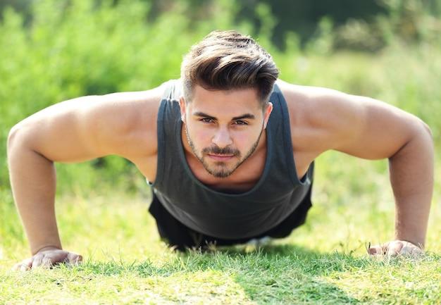 Jonge man die push-ups buitenshuis maakt