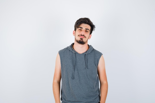 Jonge man die rechtop staat en voor de camera poseert in grijs t-shirt en er serieus uitziet