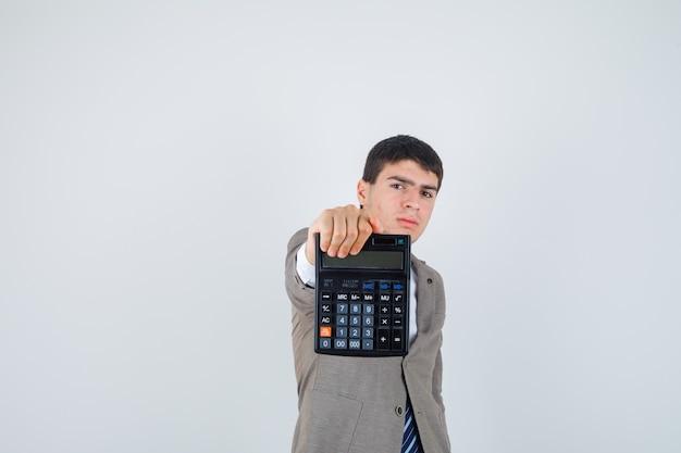 Jonge man die rekenmachine in formeel pak vasthoudt en er zelfverzekerd uitziet