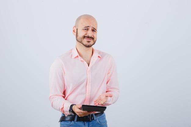 Jonge man die rekenmachine in roze shirt, spijkerbroek toont en er ontevreden uitziet. vooraanzicht.