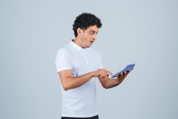 Jonge man die rekenmachine in wit t-shirt gebruikt en zich afvraagt, vooraanzicht.