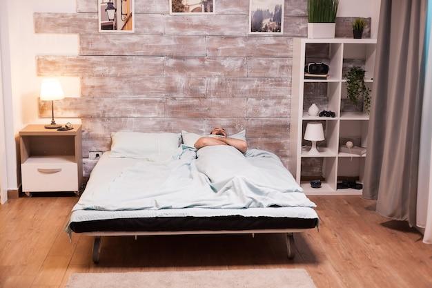 Jonge man die 's nachts goed slaapt in een comfortabel bed.