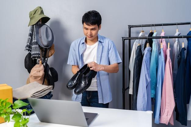 Jonge man die schoenen en kleding online verkoopt via live streaming van laptop. zakelijke online e-commerce thuis