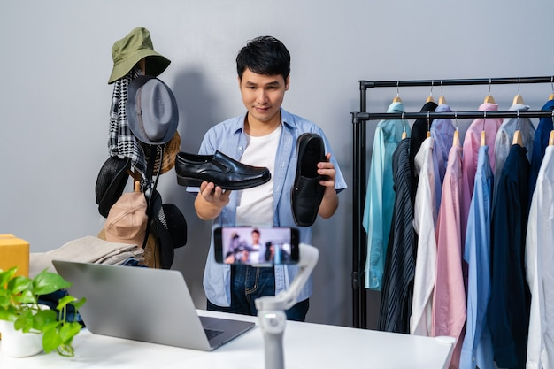 Jonge man die schoenen en kleding online verkoopt via live streaming van smartphone. zakelijke online e-commerce thuis