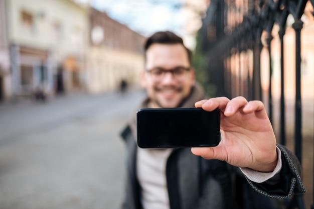 Jonge man die selfie in de stad, focus op de voorgrond.