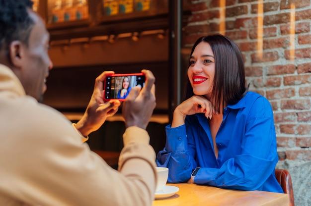 Jonge man die selfie neemt met zijn vriend die koffie drinkt in een café