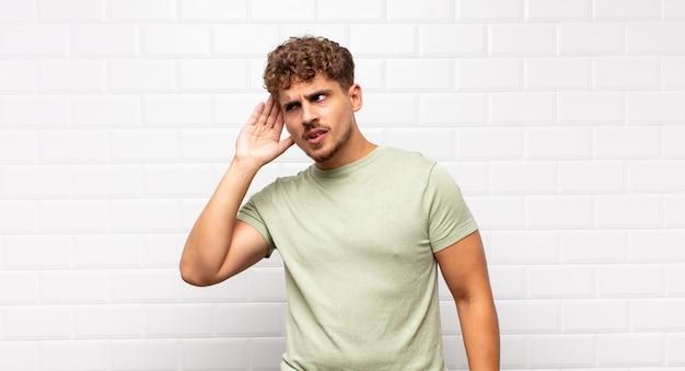 Jonge man die serieus en nieuwsgierig kijkt, luistert, probeert een geheim gesprek of roddel te horen, afluisteren