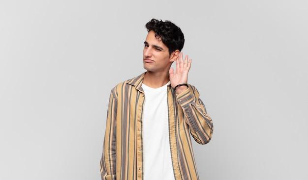 Jonge man die serieus en nieuwsgierig kijkt, luistert, probeert een geheim gesprek of roddel te horen, afluistert