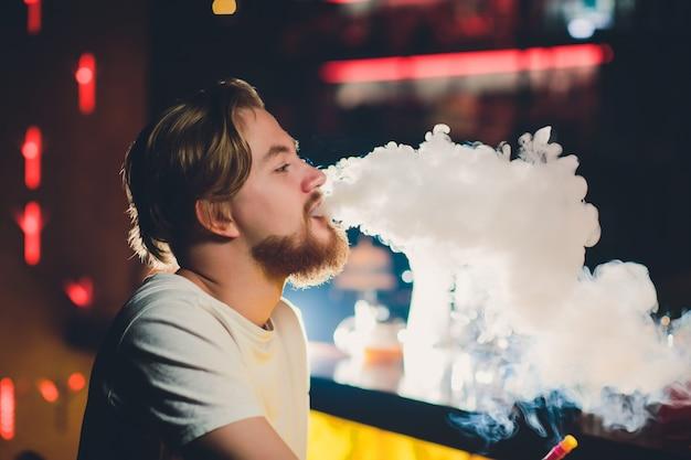 Jonge man die shisha rookt in arabisch restaurant - man die rook uitademt die van een waterpijp inhaleert.
