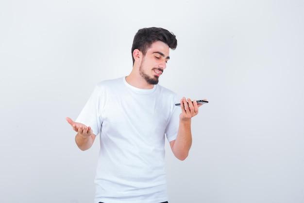 Jonge man die spraakbericht opneemt op mobiele telefoon in t-shirt en er vrolijk uitziet