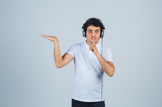 Jonge man die stiltegebaar toont, palm opzij spreidt in wit t-shirt en er verstandig uitziet. vooraanzicht.