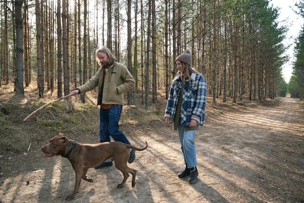 Jonge man die stok aan zijn hond laat zien en met hem speelt tijdens een wandeling in het park samen met zijn vriendin