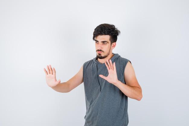 Jonge man die stopborden in grijs t-shirt toont en er serieus uitziet