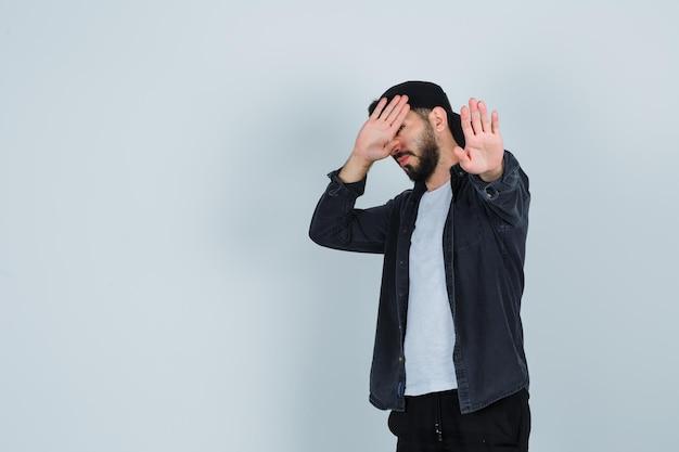 Jonge man die stopgebaar toont terwijl hij zijn gezicht bedekt met de handpalm