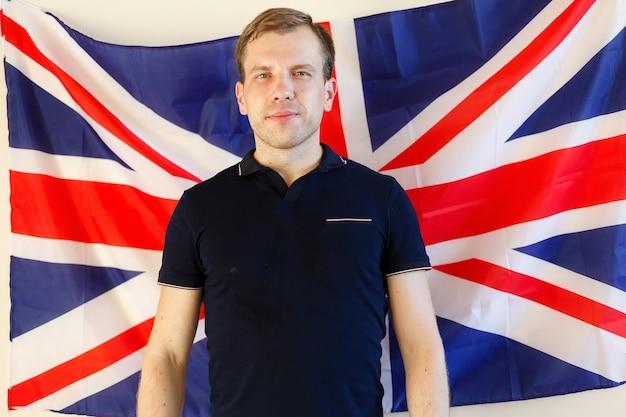 Jonge man die tegen de vlag van het verenigd koninkrijk staat