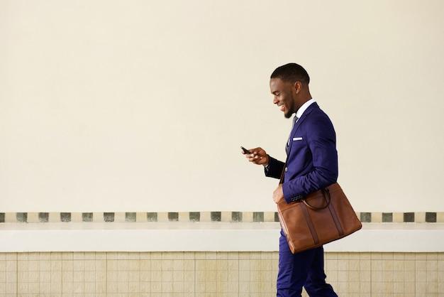 Jonge man die tekstbericht op zijn mobiele telefoon verzendt