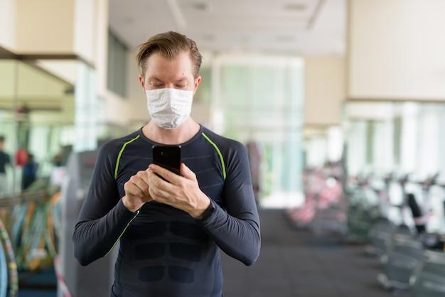 Jonge man die telefoon met masker gebruikt ter bescherming tegen uitbraak van coronavirus in sportschool tijdens coronavirus covid-19