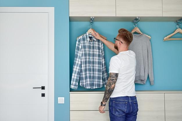 Jonge man die thuis kleding kiest
