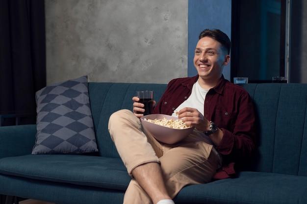 Jonge man die thuis naar streamingdienst kijkt