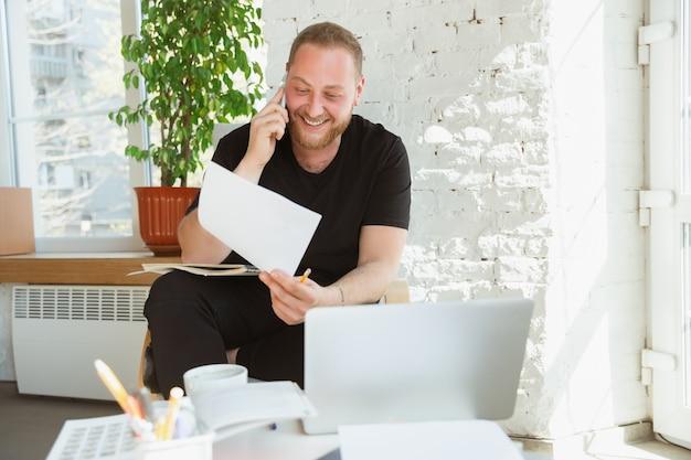 Jonge man die thuis studeert tijdens online cursussen voor managers, marketeers, kopers. beroep krijgen terwijl geïsoleerd, quarantaine tegen verspreiding van het coronavirus. met behulp van laptop, smartphone, apparaten.