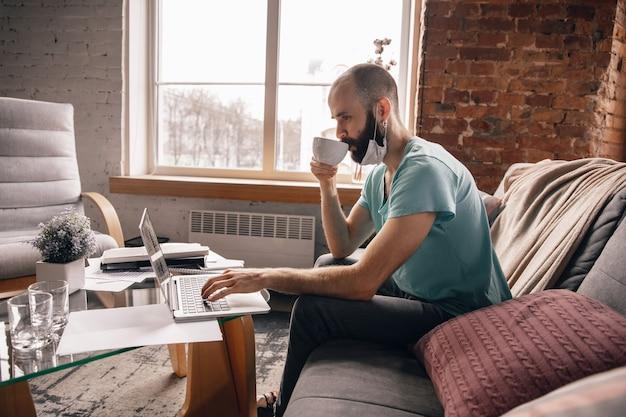 Jonge man die thuis thee drinkt terwijl hij aan het werk is