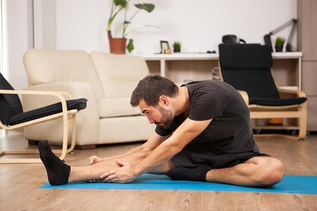 Jonge man die thuis yoga beoefent in zijn woonkamer. hij streelt en voelt zich ontspannen