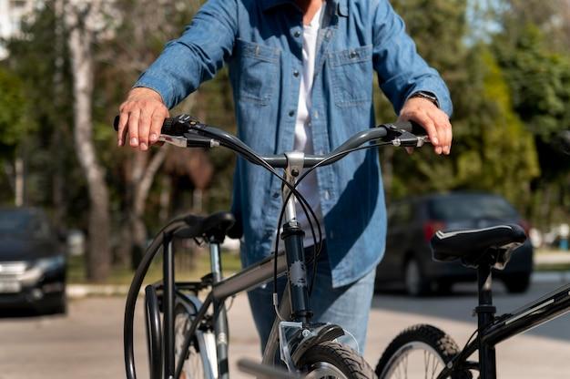 Jonge man die tijd buiten doorbrengt met zijn fiets