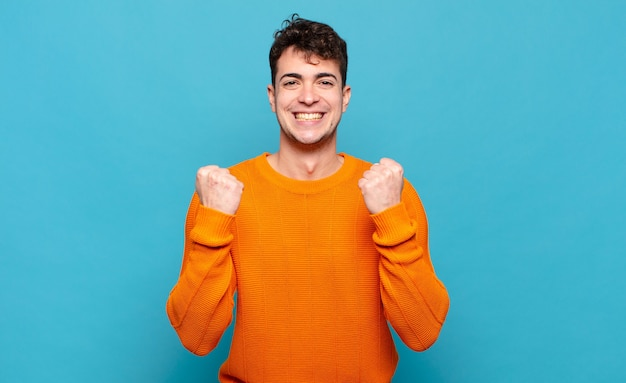 Jonge man die triomfantelijk schreeuwt, lacht en zich blij en opgewonden voelt terwijl hij succes viert