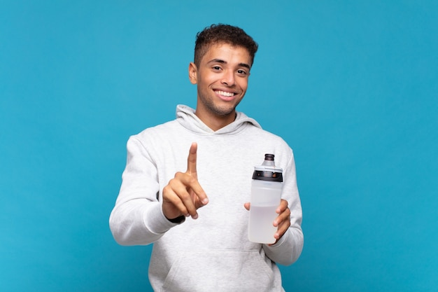 Jonge man die trots en zelfverzekerd glimlacht en nummer één triomfantelijk poseert, voelt zich een leider. sport concept