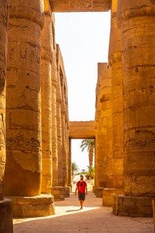 Jonge man die tussen de hiëroglifische zuilen van de tempel van karnak, egypte slentert