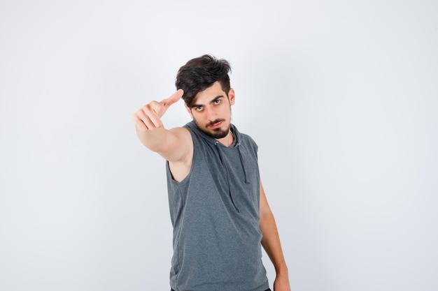 Jonge man die uitnodigt om in een grijs shirt te komen en er serieus uitziet