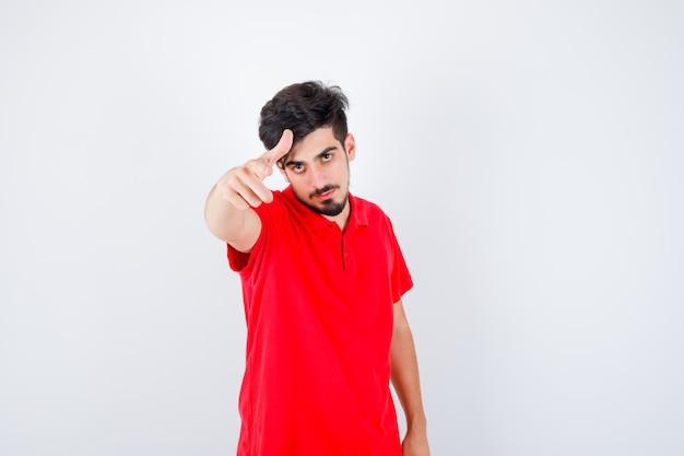 Jonge man die uitnodigt om in een rood t-shirt te komen en er serieus uitziet