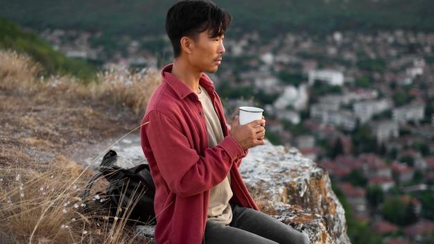 Jonge man die van landschap geniet