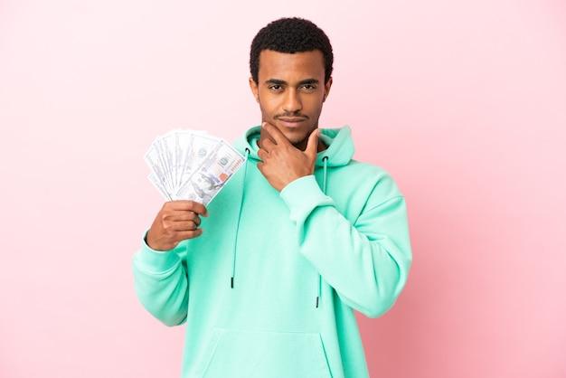 Jonge man die veel geld neemt over geïsoleerde roze achtergrond denken