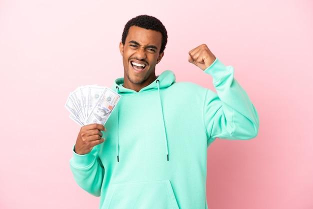 Jonge man die veel geld neemt over geïsoleerde roze achtergrond die een overwinning viert