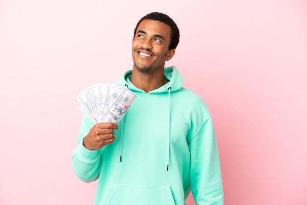 Jonge man die veel geld over een geïsoleerde roze achtergrond neemt en een idee denkt terwijl hij omhoog kijkt
