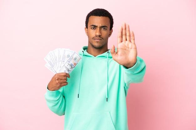Jonge man die veel geld over een geïsoleerde roze achtergrond neemt en een stopgebaar maakt