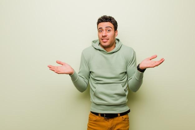 Jonge man die verbaasd, verward en gestrest kijkt, zich afvraagt tussen verschillende opties, zich onzeker voelt over de muur