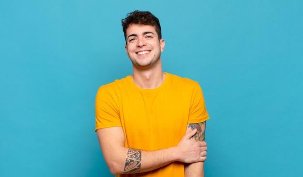 Jonge man die verlegen en vrolijk lacht, met een vriendelijke en positieve maar onzekere houding