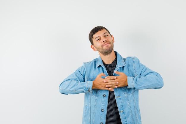 Jonge man die vingers op de borst in een t-shirtjasje vastklemt en er vrolijk uitziet