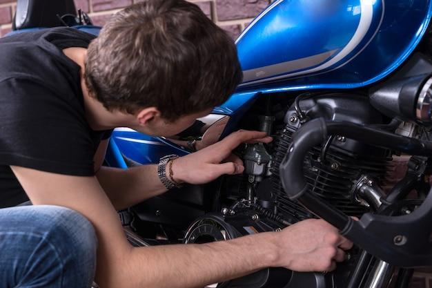 Jonge man die voorover buigt en zijn motormotor bekijkt, close-up van achteren