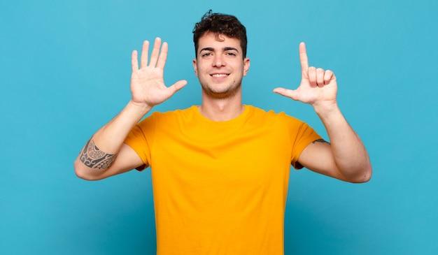 Jonge man die vriendelijk glimlacht en kijkt, nummer zeven of zevende met vooruit hand toont, aftellend