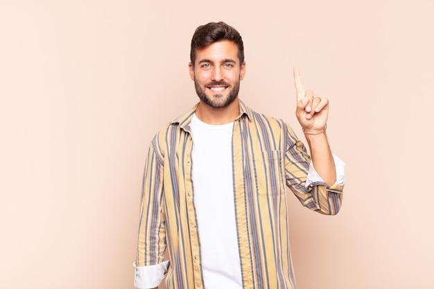 Jonge man die vrolijk en gelukkig lacht en met één hand naar boven wijst om ruimte te kopiëren