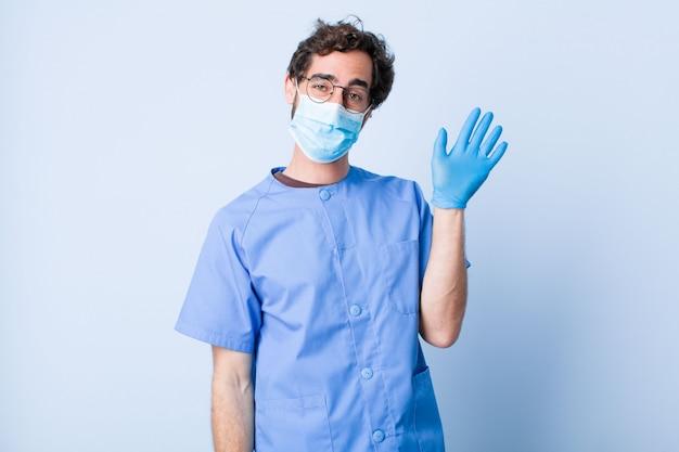 Jonge man die vrolijk en vrolijk lacht, met de hand zwaait, u verwelkomt en begroet of afscheid neemt. coronavirus concept