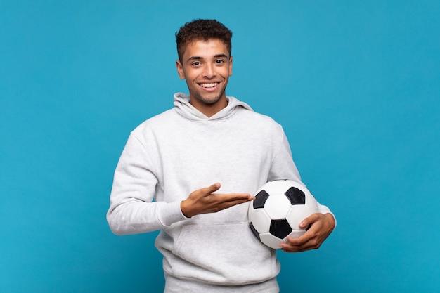 Jonge man die vrolijk glimlacht, zich gelukkig voelt en een concept in exemplaarruimte met handpalm toont. voetbal concept