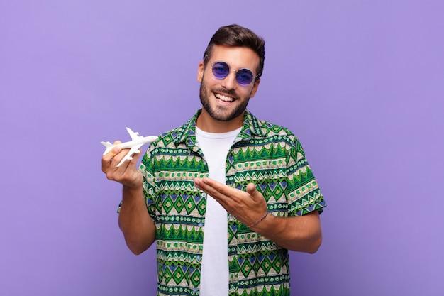 Jonge man die vrolijk glimlacht, zich gelukkig voelt en een vliegtuig met handpalm toont.